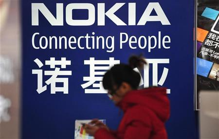 A woman walks past a Nokia advertisement board at a home appliances store in Shenyang