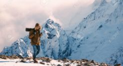 66891033 man with backpack trekking in mountains cold weather snow on hills winter hiking